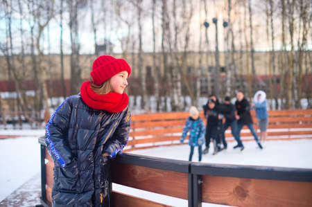 Smiling teenage girl standing near ice rink and looking at the skaters at sunny frozen day in winter.