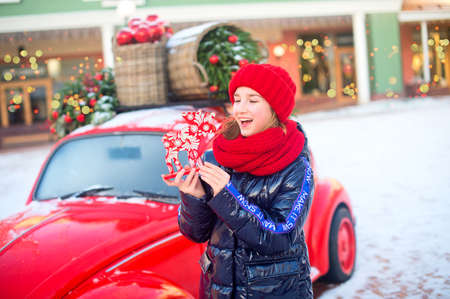 Happy teenage girl in red hat and scarf holding figure of raindeer in hands. Model standing near fashion decorated car for New Year and Christmas.