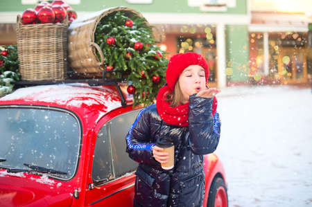 Happy teenage girl in red hat and scarf blow out snowflakes from hand. Model standing near Christmas decorated fashion car.