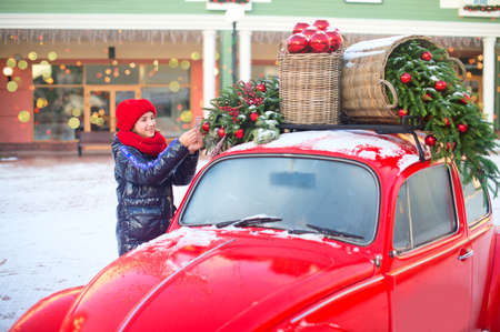 Happy teenage girl in red hat and scarf decorate fashion car for Christmas and New Year.