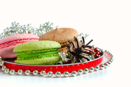 chaplet: Colorful acaroons and fir-cone in round plate with chaplet
