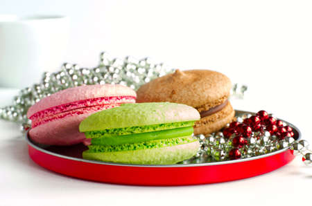 chaplet: Three colorful macaroons on red round plate with chaplet and a cup. On white.