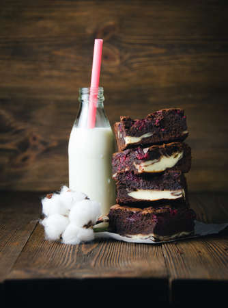 cotton flower: Raspberry brownie stuffed with cheesecake, bottle of milk and cotton flower on wooden background