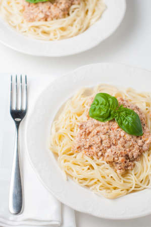 satisfying: Two plates of pasta with meat in a creamy tomato sauce and fresh basil leaves on a white background, top view