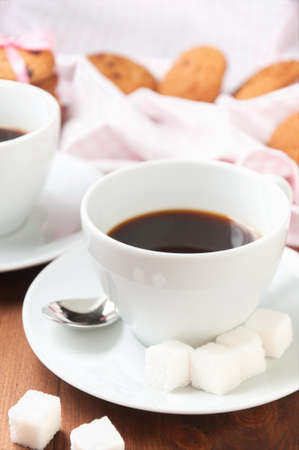 refined: Black coffee in white cup with refined sugar and oatmeal cookies on wooden table