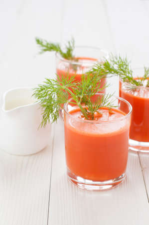 the milk jug: Carrot juice in glasses, decorated with a sprig of dill and a milk jug, on the background of white boards