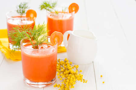 the milk jug: Carrot juice in three glasses, decorated with dill, milk jug and mimosa branch on the background of yellow napkin and white boards Stock Photo