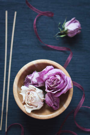 aroma bowl: Dried roses in a wooden bowl and aroma sticks on a dark blue background. Selective focus, top view. Low contrast toned Stock Photo