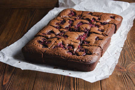 countertops: Brownie with raspberry on a baking paper and wooden countertop