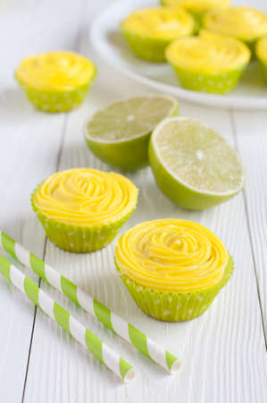 Yellow cupcakes in light green paper baking cups on table and on plate, lime and striped drinking straws on white wooden background. Selective focus Stock Photo