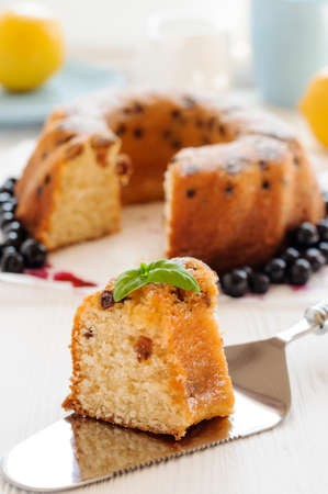 cut off: Piece of cake with raisins close-up, cut off from the cake in the background