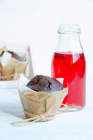 cranberry juice: Chocolate muffins in gift wrapping on light blue wooden table and cranberry juice in bottle