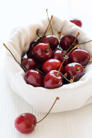 linen bag: Ripe cherries in linen bag on white background, close-up Stock Photo