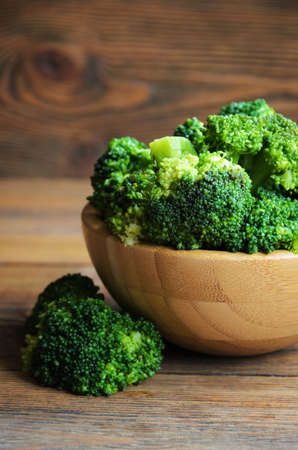 cruciferous: Fresh broccoli on wooden background, close-up. Selective focus