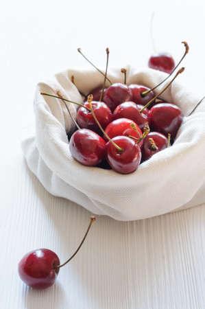linen bag: Cherries in linen bag on white wooden table Stock Photo