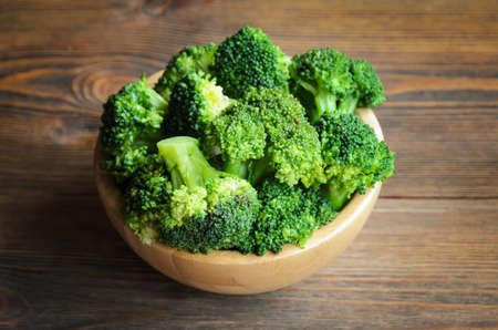Fresh broccoli in wooden bowl on the table. Selective focus Stock Photo