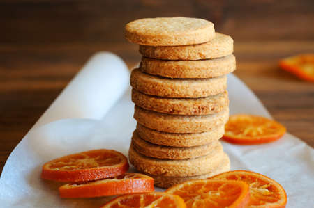 Shortbread cookies stacked and candied oranges on the table Stock Photo