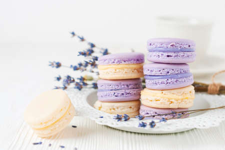 Almond cakes (macaroons) with lavender and vanilla filling on white plate. Selective focus