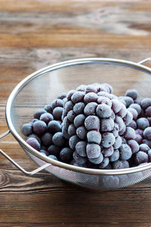 bolter: Frozen berries in sieve on wooden table
