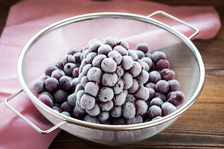 bolter: Frozen cherry berries in sieve on wooden table and pink napkin Stock Photo