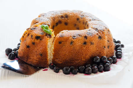 Ring cake with raisins and berries on a white background, closeup Stock Photo