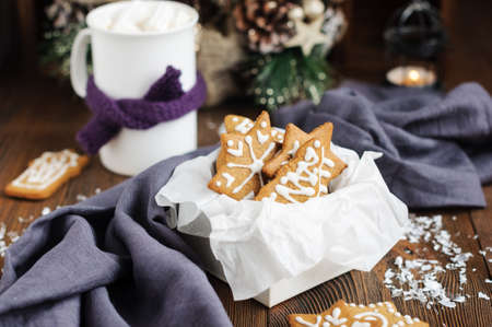 Christmas cookies in box and hot chocolate on wooden table