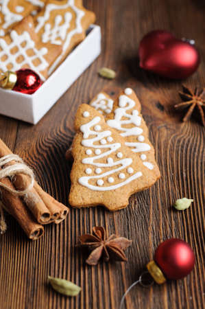 gingery: Spiced biscuits in shape of Christmas trees, decorations, on wooden table Stock Photo