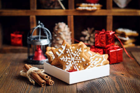 Christmas cookies with decorations, cones, wreaths and burning candle on wooden background