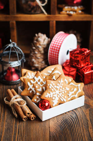Christmas biscuits with decorations, cones, wreaths and burning candle on a wooden background