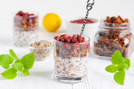 wild oats: Homemade granola with wild strawberries and yogurt in glass on white wooden table