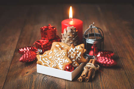 Still life with Christmas biscuits, decorations, pine cones, wreaths and burning candle on wooden background, vintage toned