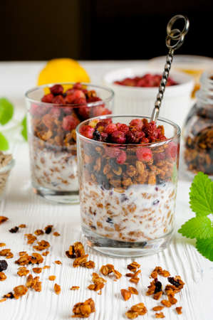 Two glasses of granola with yogurt and wild strawberries on table