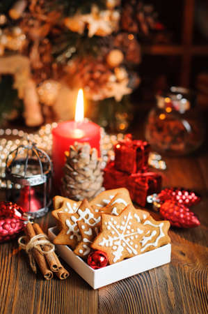 Christmas cookies with decorations, cones, wreaths and burning candle on wooden table