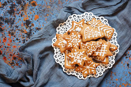 Christmas biscuits in plate and blue cloth on table