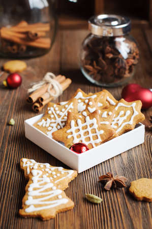 Spiced biscuits in shape of Christmas trees and stars with icing and decoration on the wooden table