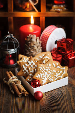 pine wreaths: Christmas still life with biscuits, ornaments, pine cones, wreaths and burning candle on a wooden background