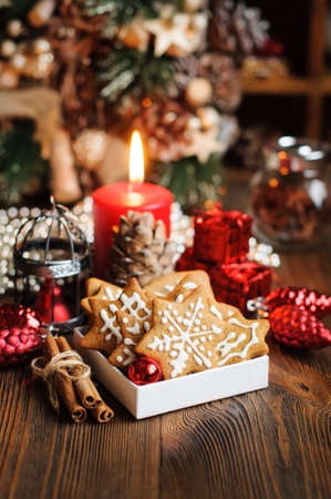 Christmas still life with cookies, decorations, pine cones, wreaths and burning candle on wooden background, with copy space for text