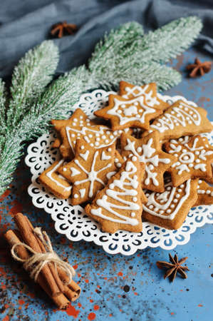 Christmas cookies in plate and fir branch on blue background Stock Photo