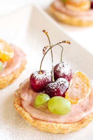 Fruit mini tarts with cherry on a white wooden table. Close-up