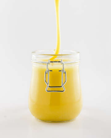 white backgroung: Honey in glass jar, flowing down on white backgroung Stock Photo
