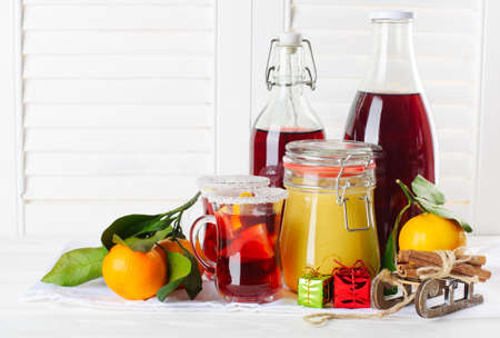 cranberry juice: Cranberry juice in two glasses and bottles, honey in jar, mandarins and Christmas decorations on white wooden table