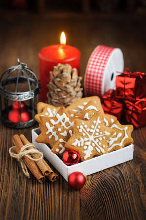 Still life with Christmas biscuits, decorations, pine cones, wreaths and burning candle on wooden background Stock Photo