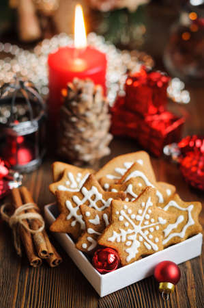 Christmas still life with biscuits, ornaments, pine cones, wreaths and burning candle on a wooden background