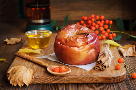 Apple baked with honey. Rowanberry and dry autumn leaves on wooden cutting board Stock Photo