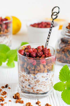 wild oats: Homemade granola with yogurt and wild strawberries in glass, mint leaves and baked oat-flakes scattered on white wooden background Stock Photo
