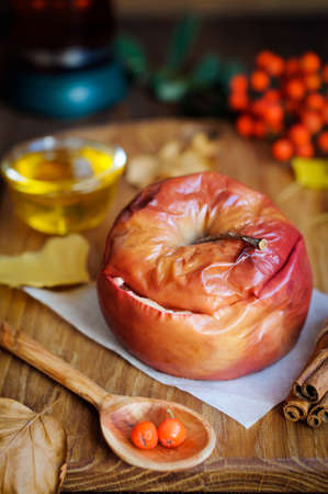 Autumn still life of apple baked with honey. Rowanberry and dry autumn leaves Stock Photo