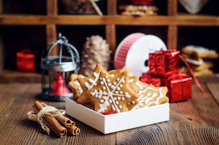 Christmas spiced biscuits in shape of stars with icing and decoration on the wooden table