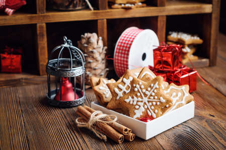 Gingerbread cookies in box and Christmas decorations on wooden background