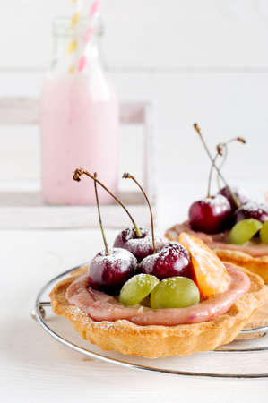 Cherry mini tarts with fruits and milk drink in bottle, white background