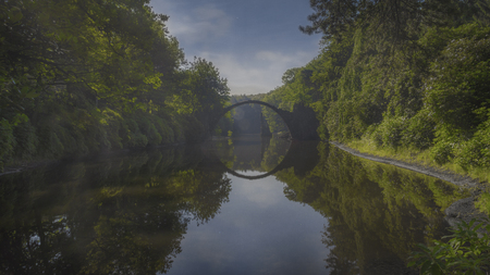 a old bridge reflecting a perfect circle in the woods